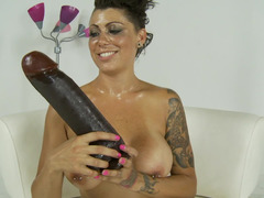 A boobalicious lady is pushing a big ramrod shaped toy deep in her love hole