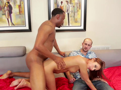 A redhead is getting a black phallus in her next to her cuckold man