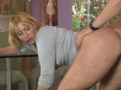 A blonde is undressed on the desk and she is fucked hard by her partner