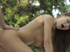 Two people are on top of each other on the grass, having outdoor sex