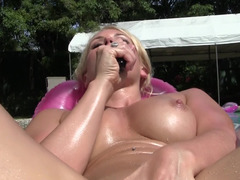 A blonde that loves jerking off in the pool is tanning in the sun