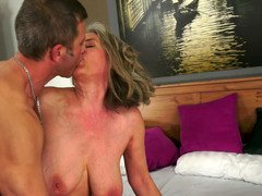 A granny with saggy breasts is getting penetrated on the bed