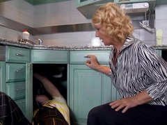 A blonde grown-up woman removes her clothes and moreover fucks in the kitchen