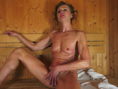 A unshaved granny is getting licked and fucked in a sauna by a 18-19 year old