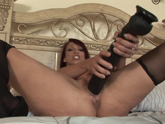 Nicki Hunter satisfied by the massive dildos in her bed