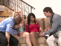 Two chicks are in a hot foursome, getting fucked on the sofa