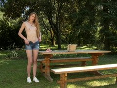 A hot chick removes her clothes and then masturbates outdoors