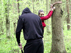 Whipping a Belt of a sub woman strapped to a Tree in a Dense Forest