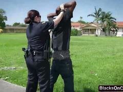 Cops with milk sacks sharing large black rod outdoors