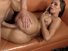 A chick is getting a huge cock inside her wet pussy on the sofa