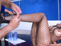 A woman with a fishnet suit is getting her pussy lips entered on the desk