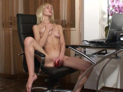 A blonde is nude in the office and she is having lots of fun
