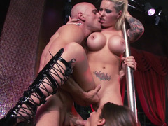 A pair of babes work on a stripper pole with a huge guy in a three-way