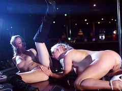 A couple of chicks work at a strip club around a pole and besides kiss one one other